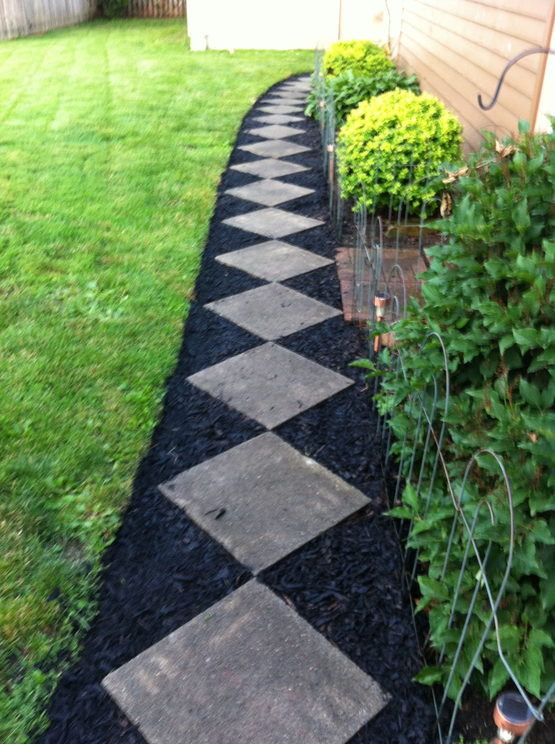 Patio stones placed corner to corner for an inexpensive walk with a