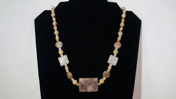 """This necklace uses stone circles, squares, and rectangles (the largest is approx. 1.125"""") with stone and plastic sphere spacers and glass seed beads. The piece is 20"""", fully beaded, with bronze lobster clasp."""