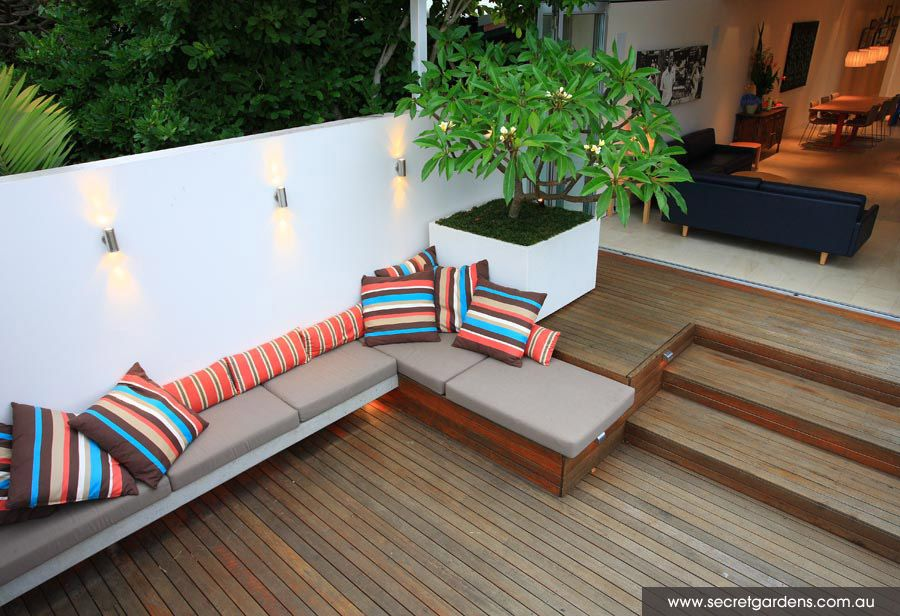 Cushioned benches & planter with tree. Ideally room for waterproof storage under the benches.
