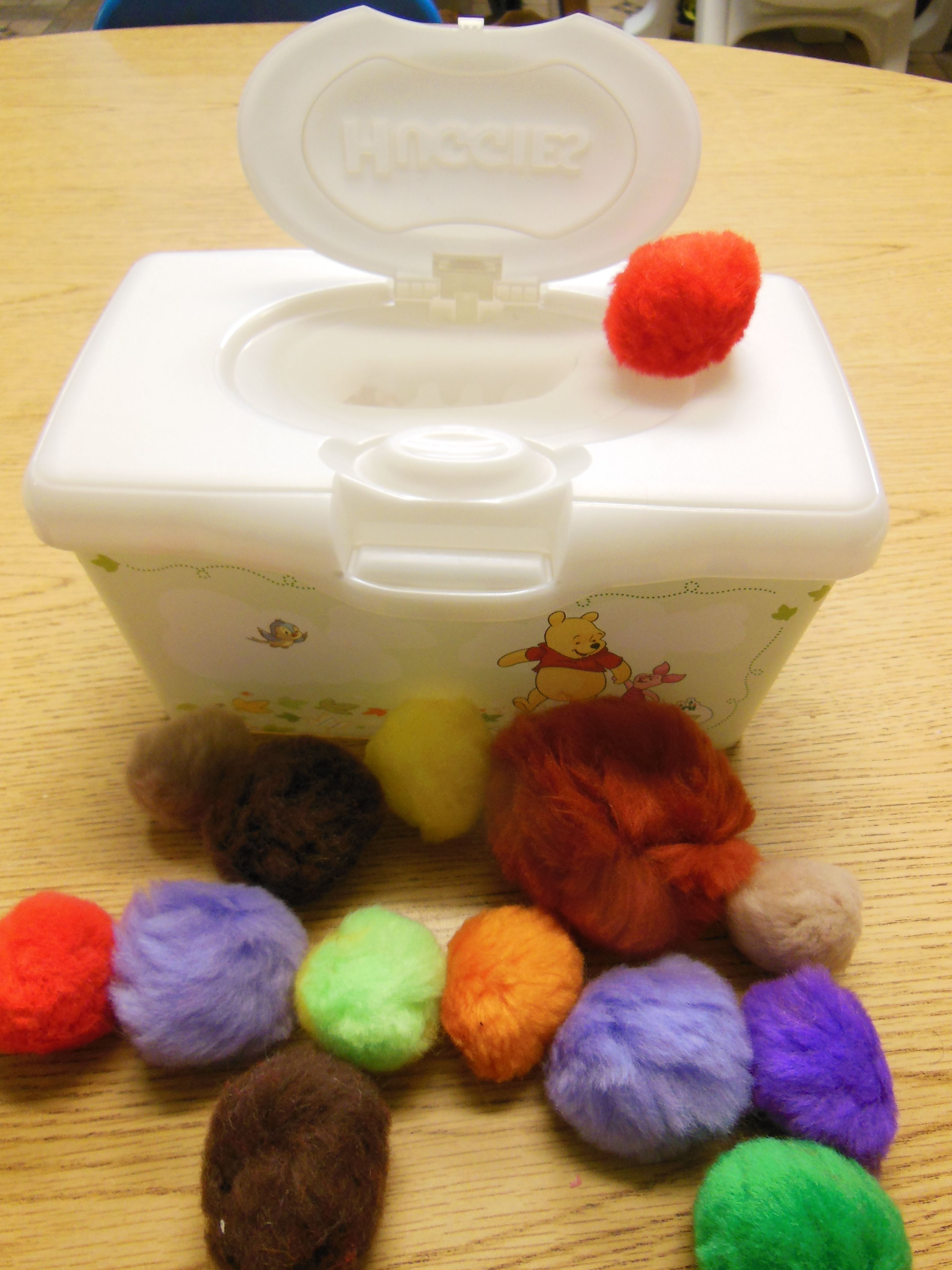 Toddler toy, reuse cute baby wipes container and add large pompoms
