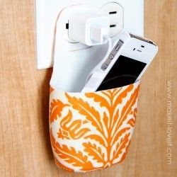 cell phone chargers are tucked away with this holder made out of a lotion bottle!-cute.