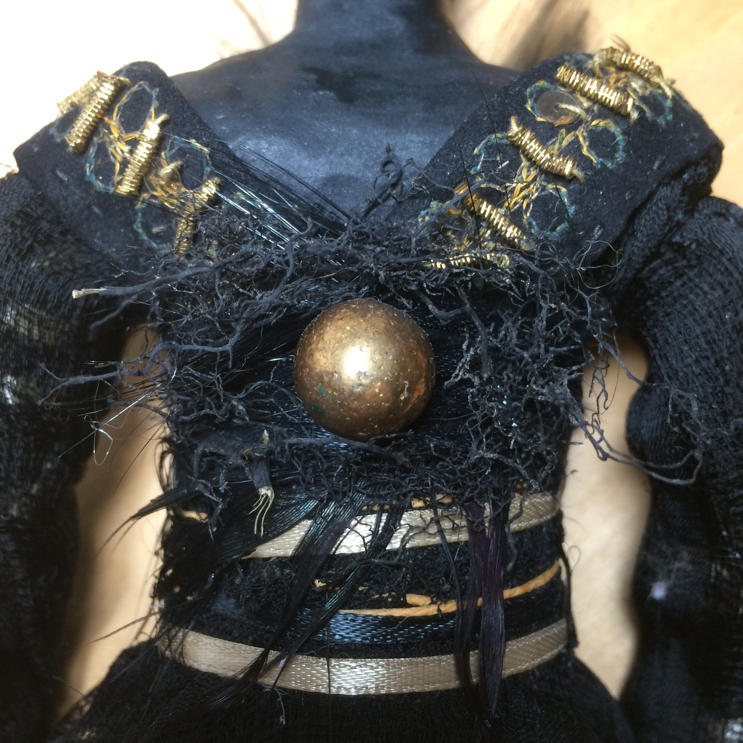 Detail of Black Beauty rabbit art doll. Made from vintage black suede gloves with gold wire trim and button, black gauze scarf, 1950's vintage hat feathers, beads, black roots from a fallen tree, ribbon, hemp twine, paper cl…