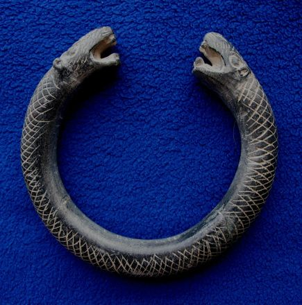This bracelet is about 11 cm diameter and has been crafted from black chlorite in a snake or dragon (note the small ears) design.  It seems likely that this bracelet was meant as a burial piece, as chlorite is not durable for jewellery - in fact this bracelet was found broken into three pieces.  It dates from the 3rd Millennium BC and was found in Afghanistan.