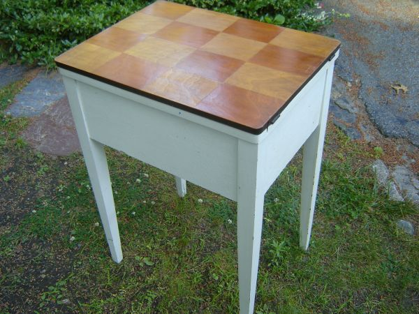 An Old Sewing Machine Cabinet Painted White With A Checkerboard
