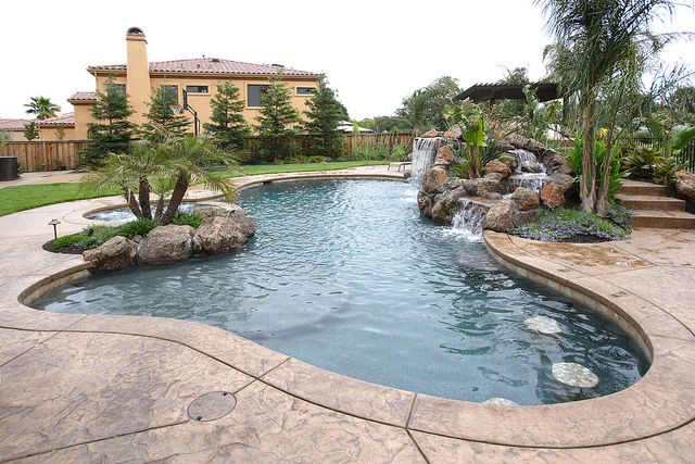 A Pool With A Waterfall In A Luxury Backyard Pool Landscaping Swimming Pool Designs Swimming Pools Backyard