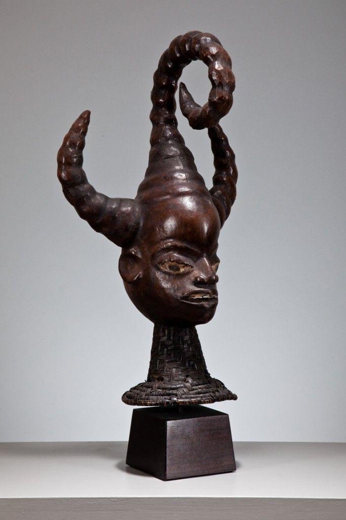 AN EKOI HEAD CREST  19TH century Efut-Ibibio people, Cross River Region, Nigeria Wood, fibre, metal, animal skin and horn 48 cm high  Provenance: Henri Kamer, Paris and New York
