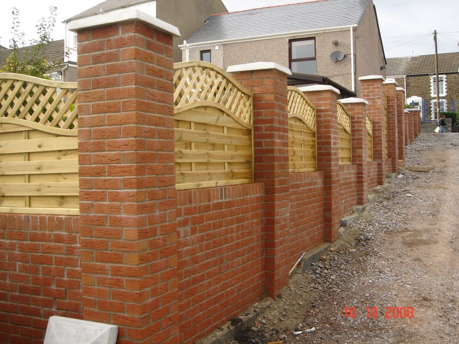 Garden wall with brick pillars and decorative wooden for Designs for brick garden walls