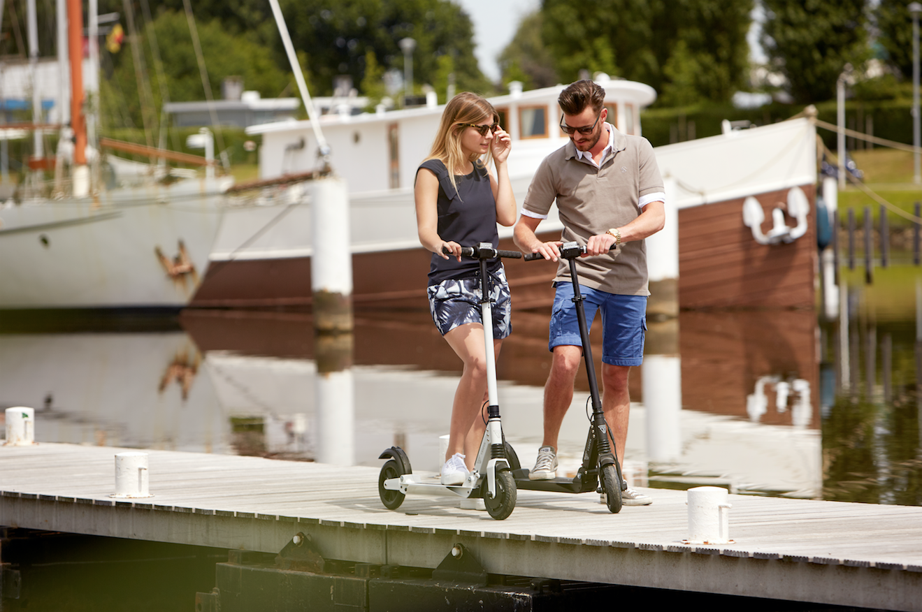 Vesper electric scooter in between the boats
