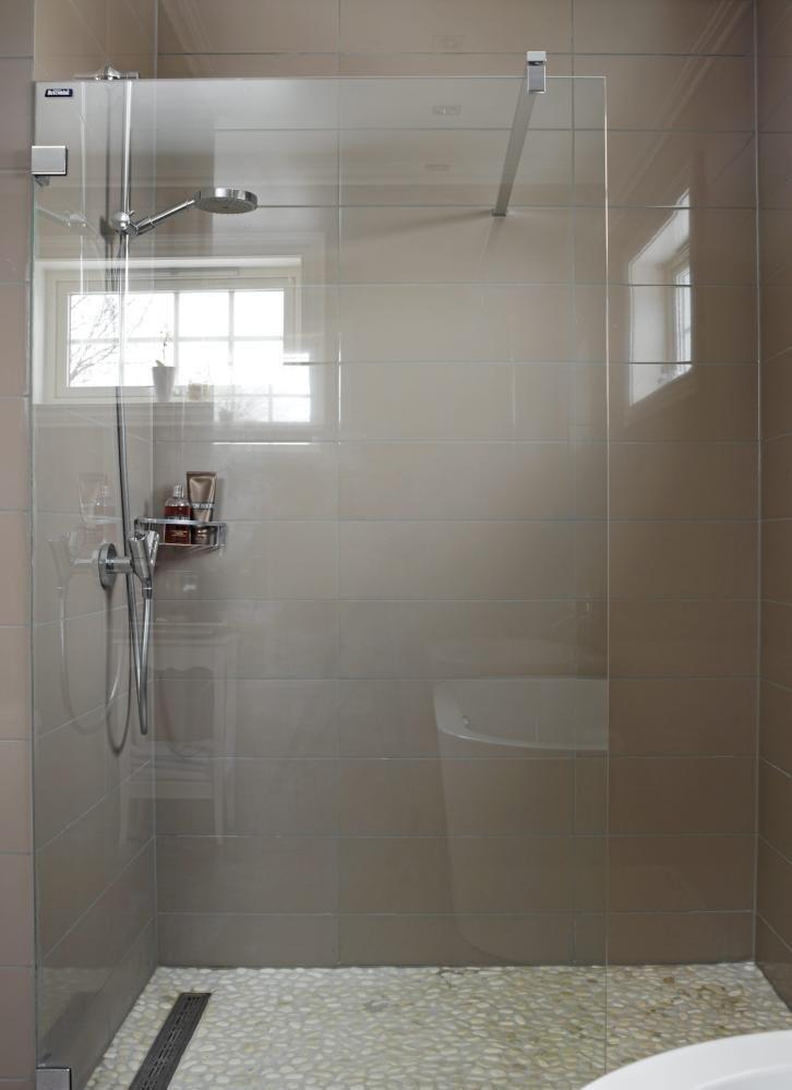 Photo of Dusjen er enkel, og nesten usynlig med den rene glassdøren. Den matte gråfarge…