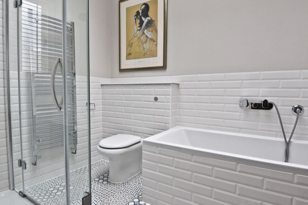 White statement tiles complemented with mosaic floor tiles