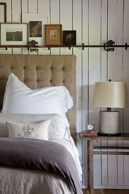 Bedroom...natural tones...tufted burlap headboard, gray & white linens, rustic side table...iron bar above bed with photos.