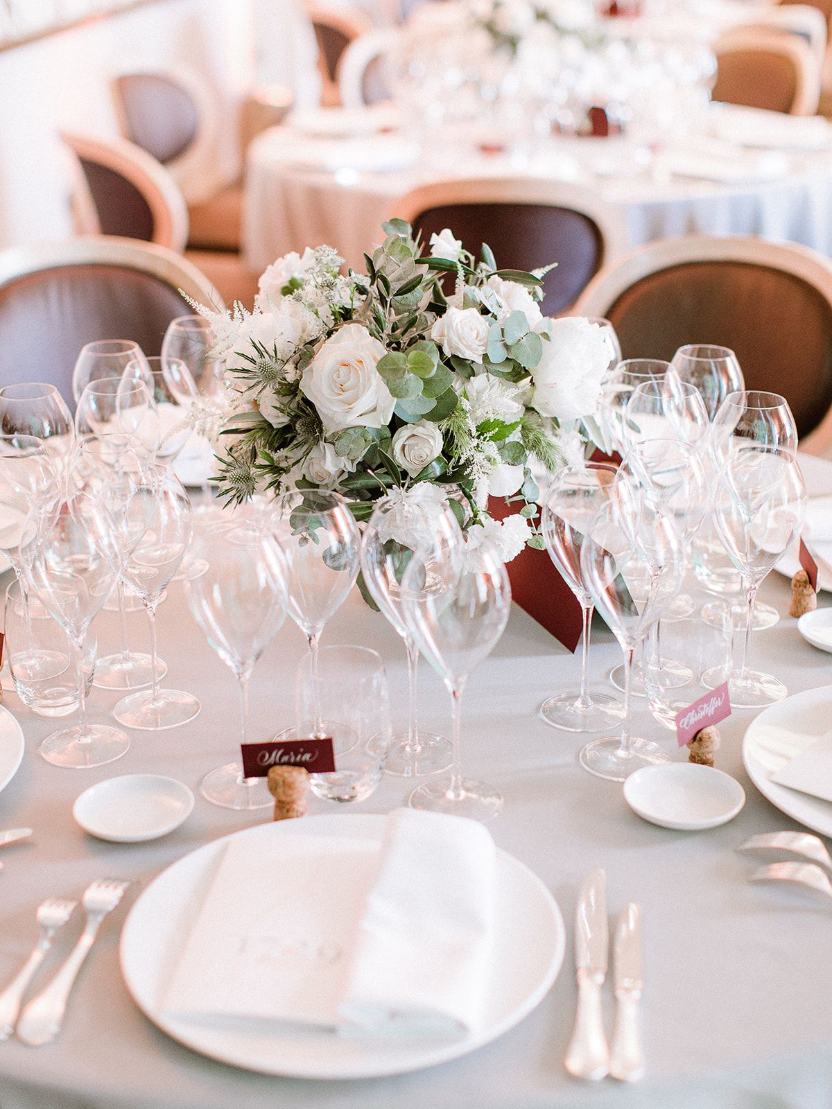 Low wedding centerpiece with white flowers and greenery