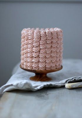 I wish I knew how to make frosting like this. Nice wooden cake stand too!