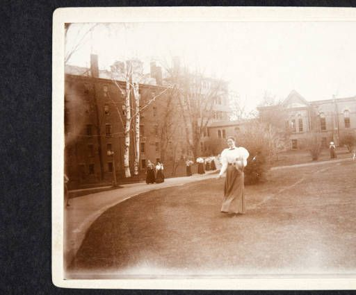 Mount Holyoke Seminary, view of students walking on grounds between north wing of main building (left) and rear of library (right), seen from the east :: Archives & Special Collections Digital Images :: circa 1886-1896