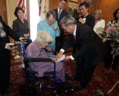 Octogenarian Phyllis Lyon (standing, 2nd L) watches as her partner Del Martin (bottom) signs their gay-marriage certificateIn  front of San Francisco county clerk Edwin Lee during the first legal  same-sex marriage ceremony at San Francisco City Hall in San Francisco,  California.The first gay coupl