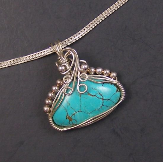 Blue Parrot Sterling Silver and Turquoise Wire Wrapped Pendant   Beautiful blue turquoise wire wrapped pendant in sterling silver wire with sterling silver bead accents. The turquoise cabochon has a beautiful golden matrix. The chain is for display only and not included.  The pendant measures 1 5/16 inches long by 1 3/16 inches wide.  One of a kind.