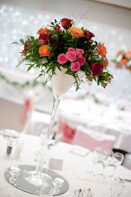 Martini Glass Centre Piece Filled With Floral Arrangement On A Round Mirror  Base.