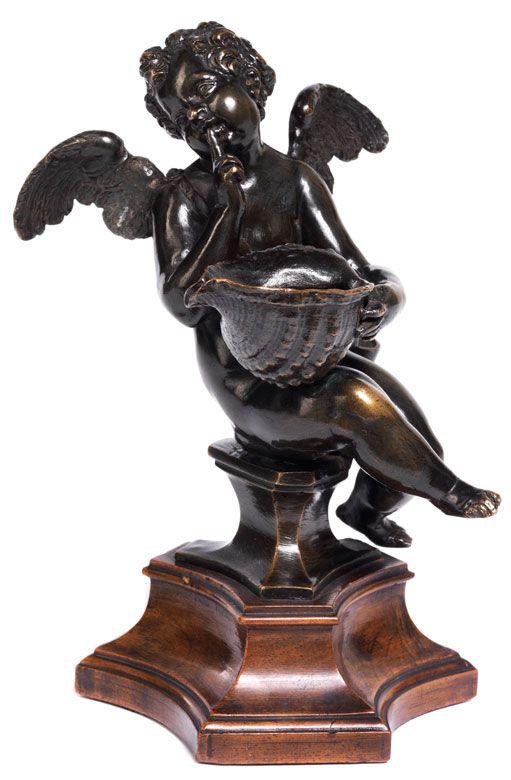 BRONZETINTENFASS Höhe mit Holzsockel: 20 cm. Venedig, um 1600. Auf dreiseitigem, mitgegossenem Bronzesockel ein geflügelter Armorknabe, der eine...