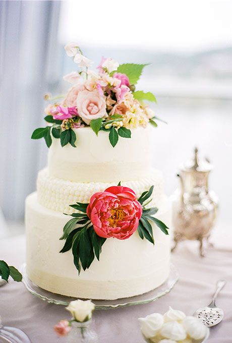 A Three Tiered White Wedding Cake With Fresh Flowers Created
