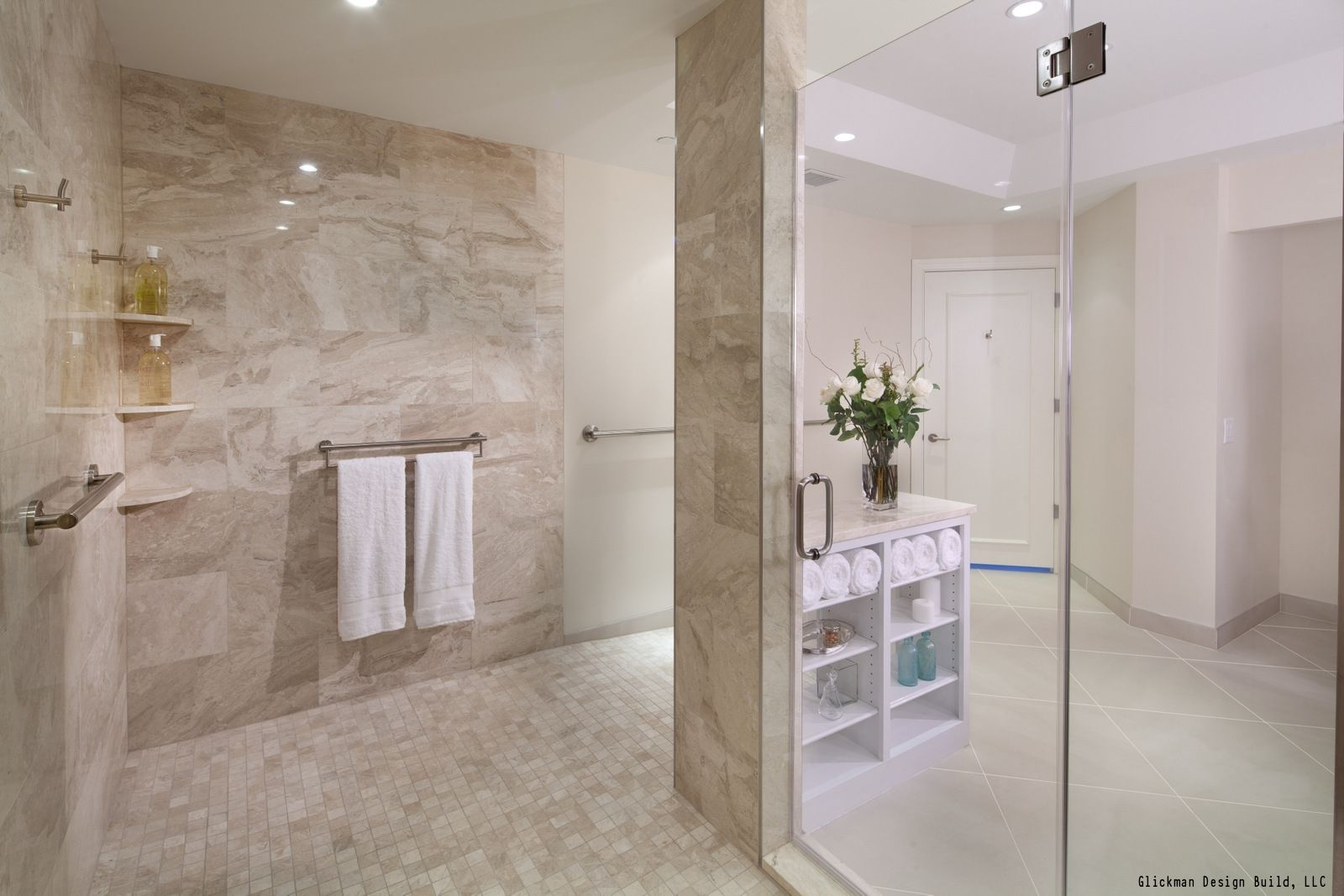 A giant walk in shower with glass shower doors. The bathroom is ...