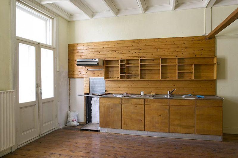 File interieur achterkamer met houten keukenwand en keukenkastjes