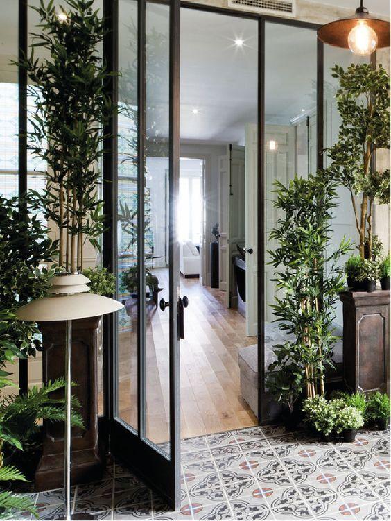 L\'extension vitrée de cette maison a été envahie de plantes vertes ...