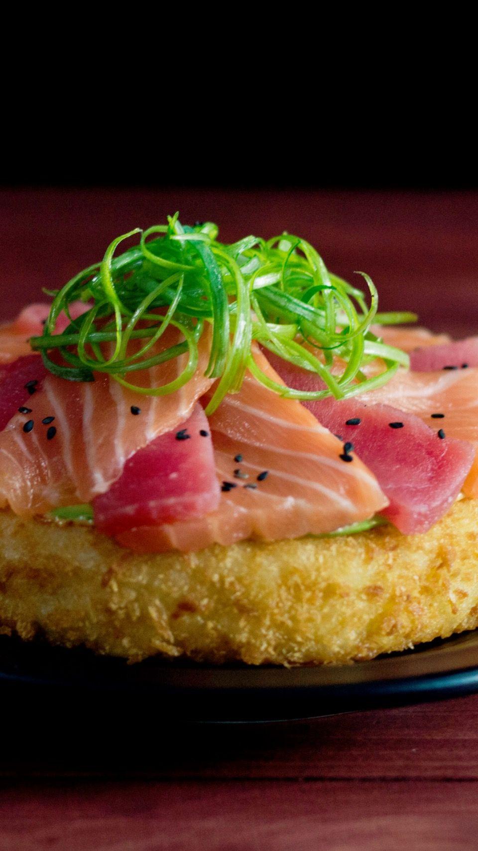 A crispy rice patty topped with avocado, fresh tuna and ...