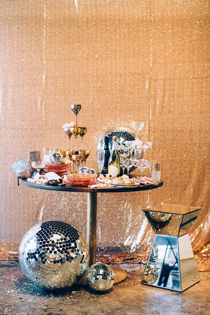 New Year's Eve party decor idea - gold, glitter backdrop, disco ball decor and champagne tower {Courtesy of Glitter Guide}