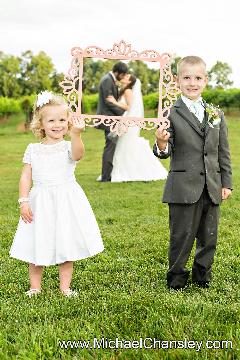 ring bearer and flower girl hold up photo frame with bride and groom ...