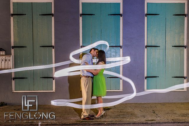 Creative engagement photography pose with light painting in the French Quarter of New Orleans
