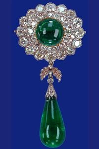 Originally used as separate and detachable parts of a stomacher made for the Duchess of Teck in the early 1890s. Queen Mary joined the two elements (comprising two of the Cambridge emeralds) into a brooch which she wore pinned below the Delhi Durbar stomacher.