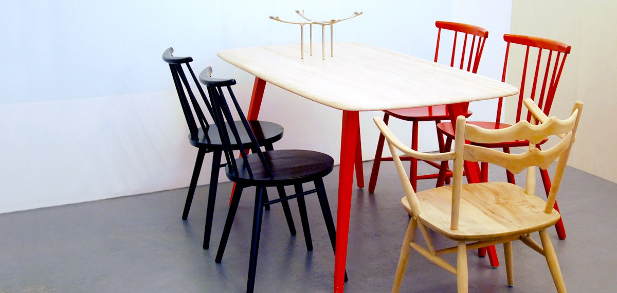 Ercol plank table, natural wood finish top with red lacquer legs.