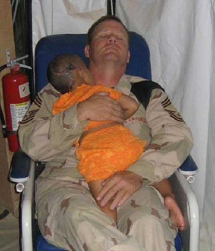 He is a Chief Master Sergeant John Gebhardt in the USAF serving in Afghanistan  As high as you can go in enlisted ranks (E-9)    John Gebhardt's wife, Mindy, said that this little girl's entire family was executed.    The insurgents intended to execute the little girl also, and shot her in the head...  But they failed to kill her.    She was cared for in John 's hospital and is healing up, but continues to cry and moan.    The nurses said John is the only one who seems to calm her down, so…