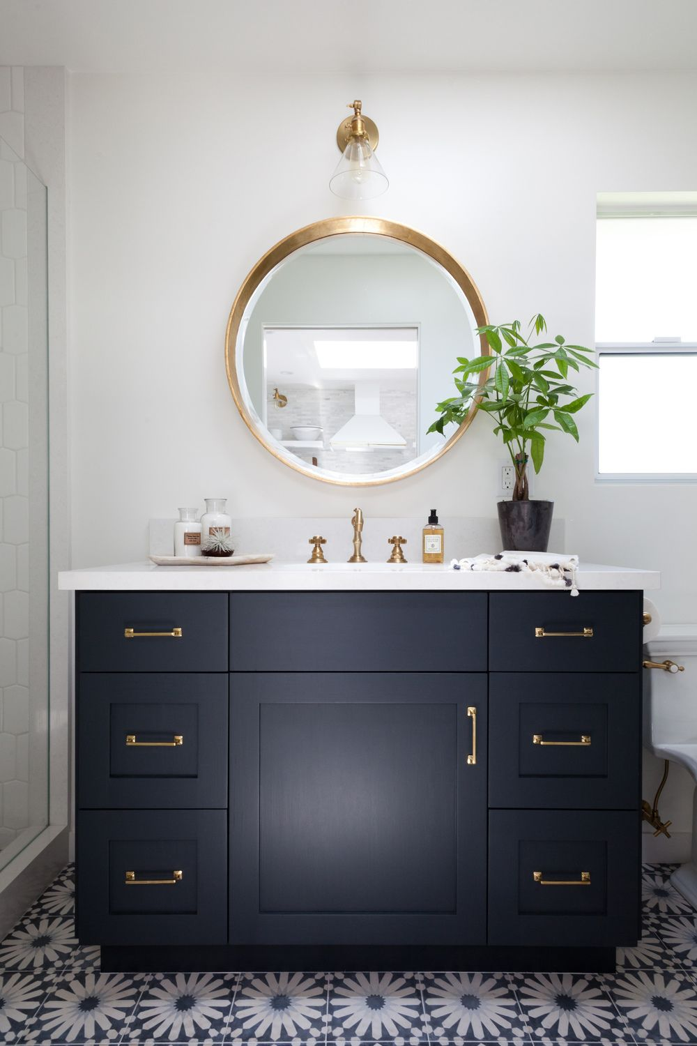 Blue and white bathroom with round mirror and brass accents. Love ...