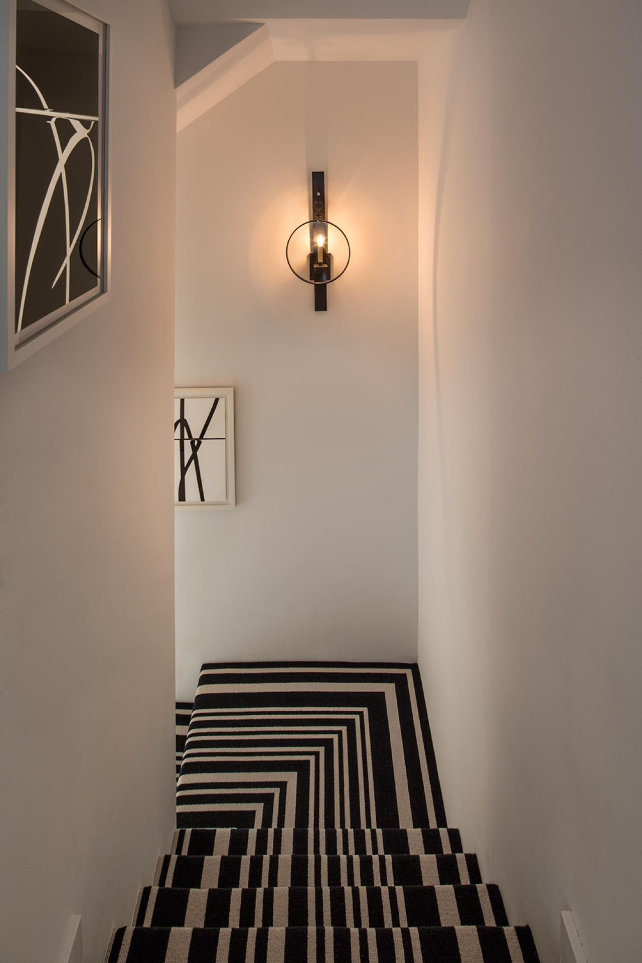 In The Stairwell, A Black And White Striped Stair Runner Makes A Bold  Visual Statement