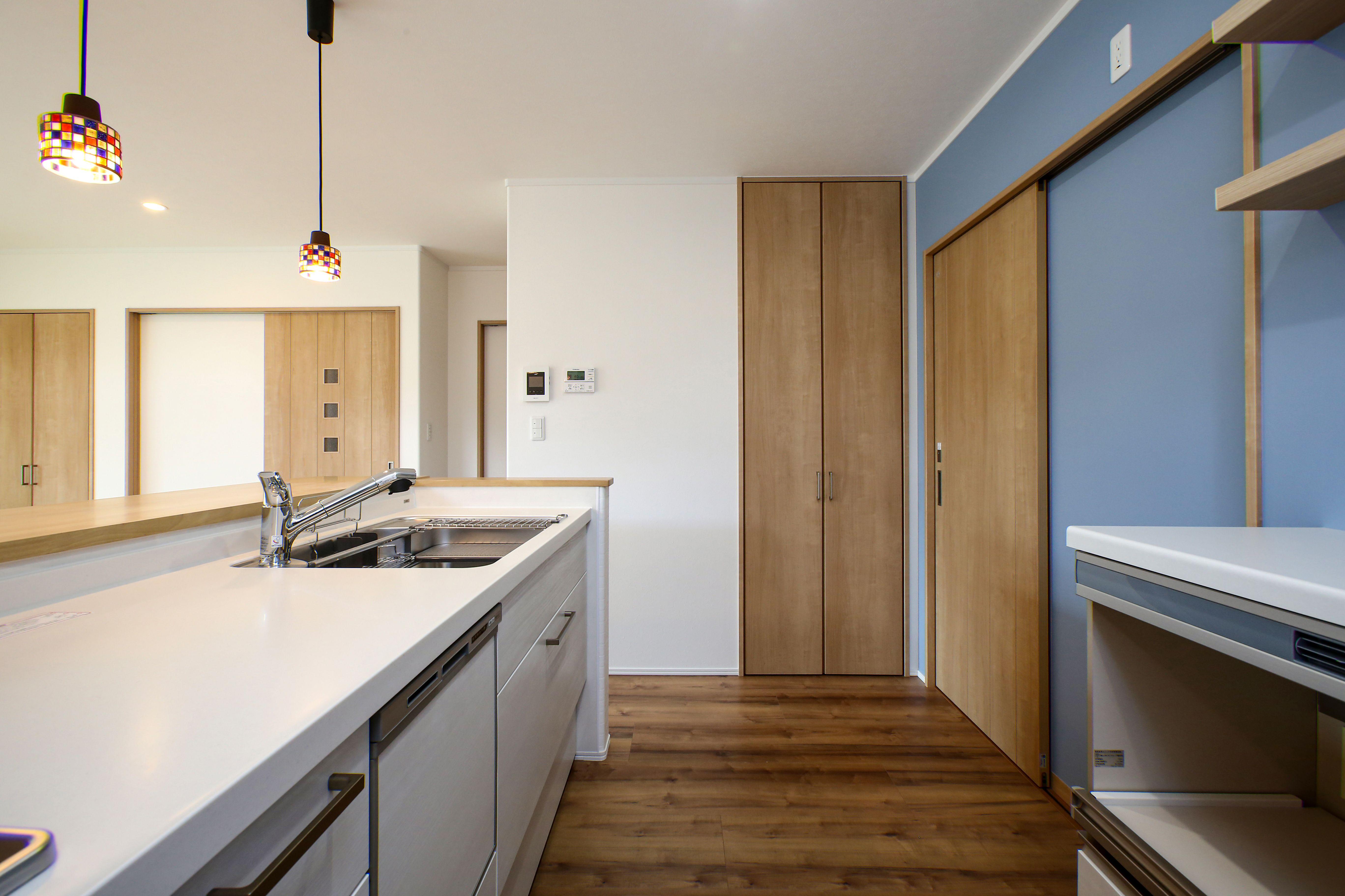 シンプルな白のキッチンに ブルーのアクセントクロスが映えますね