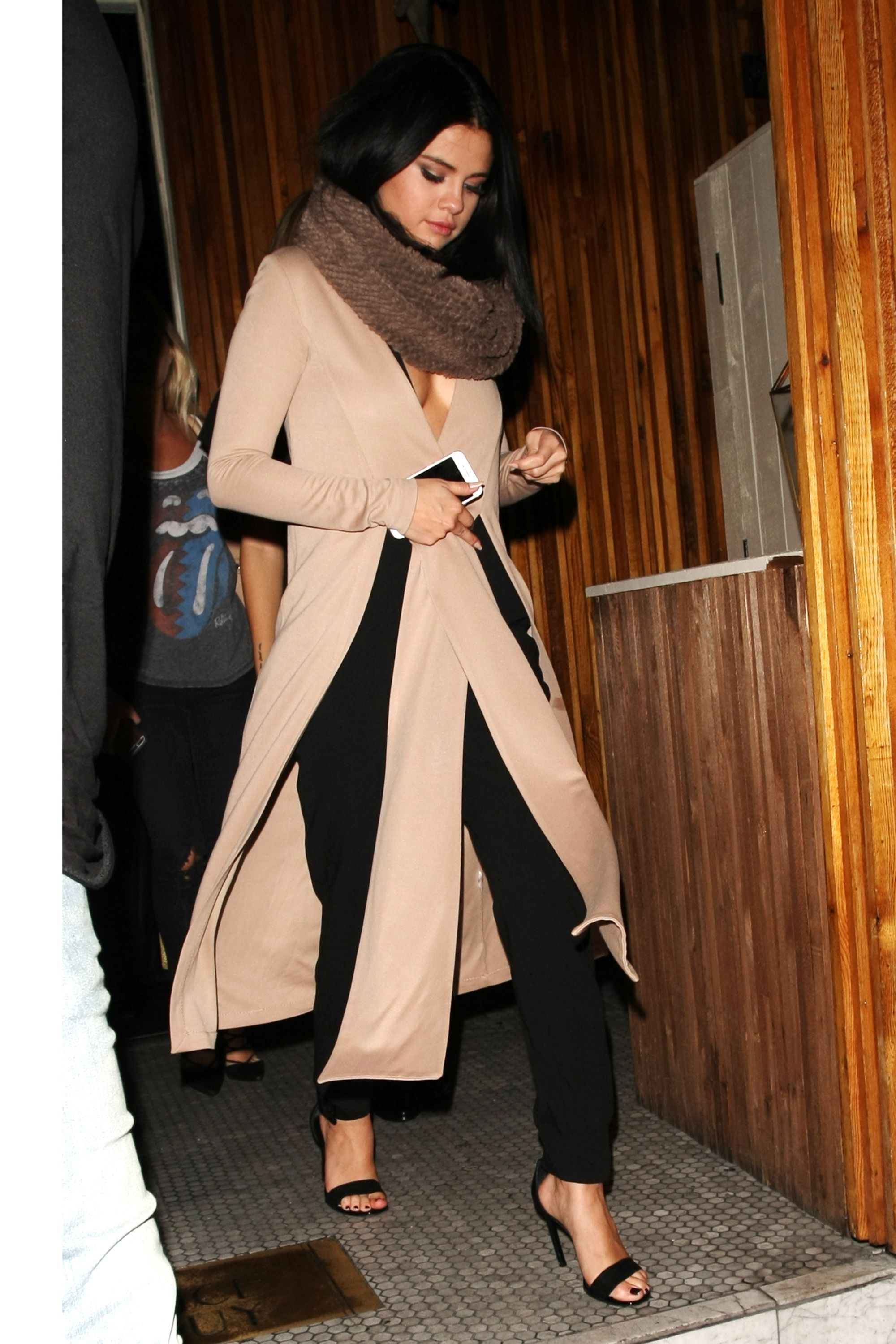In a fur scarf, plunging camel sweater and black pants. - HarpersBAZAAR.com