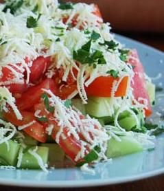 (Shopska Salad) 4 ripe tomatoes 2 long cucumbers 1 onion 1 red or green pepper 1/3 bunch of parsley 2 tablespoons olive oil 3 tablespoons of red wine vinegar 1 cup Bulgarian cheese (or feta cheese)