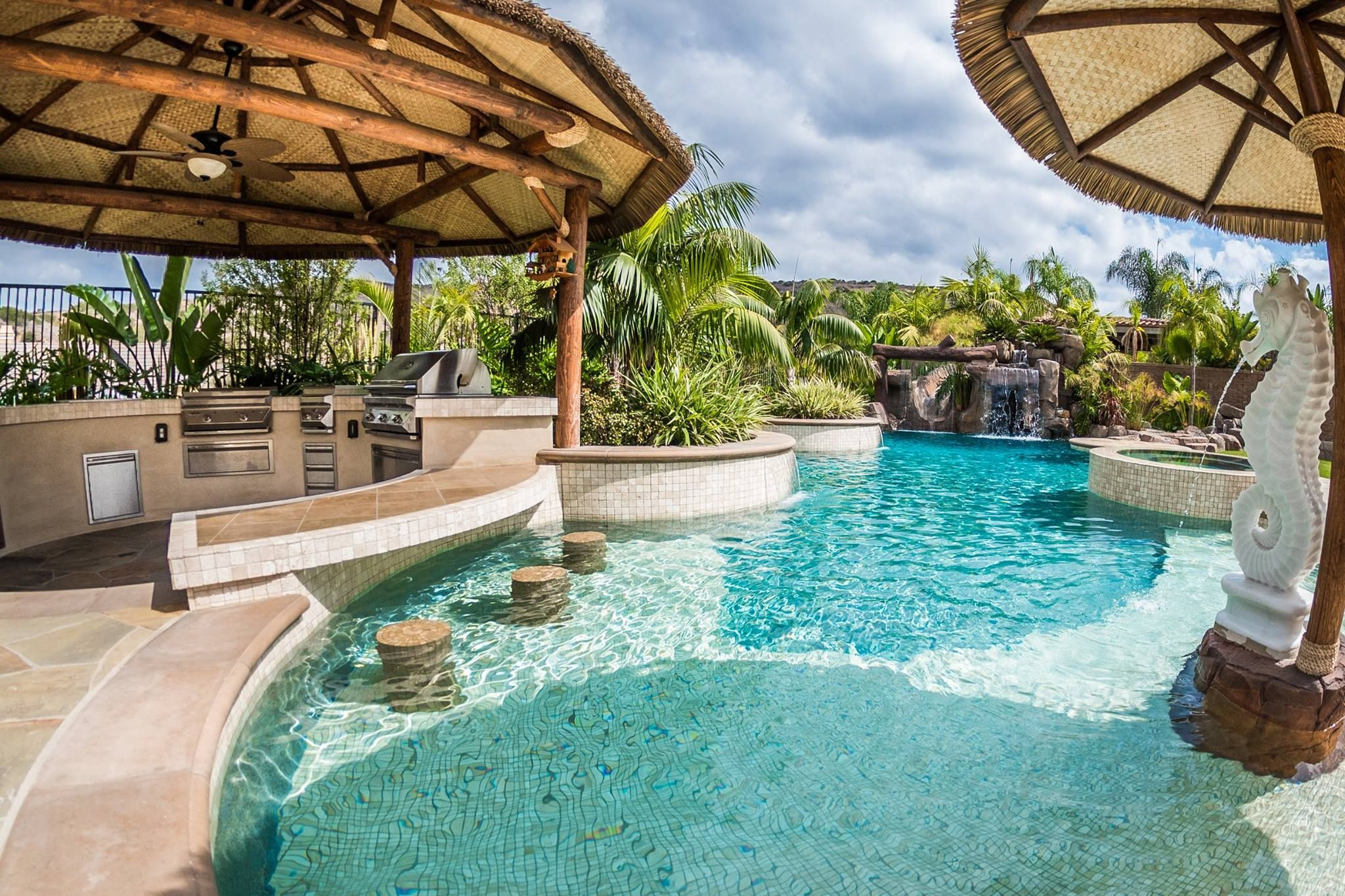 materials tropical beach entry custom swimming pool with a perimeter flow spa grotto rock slide and waterfalls custom outdoor kitchen with swim up bar - Swimming Pools With Grottos