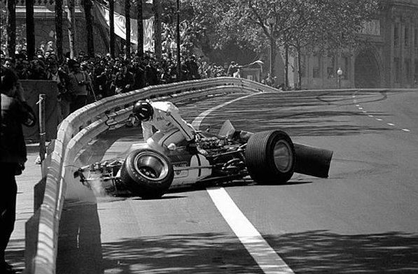 Graham Hill (GBR) climbs from the wreckage of his Lotus 49B, his rear wing having collapsed on the ninth lap. The accident illustrated the worthiness of Armco barriers and the inherent dangers of movable high aerofoils, which were banned shortly thereafter. Spanish Grand Prix, Montjuich Park, 4 May 1969. World © Sutton Motorsport Images