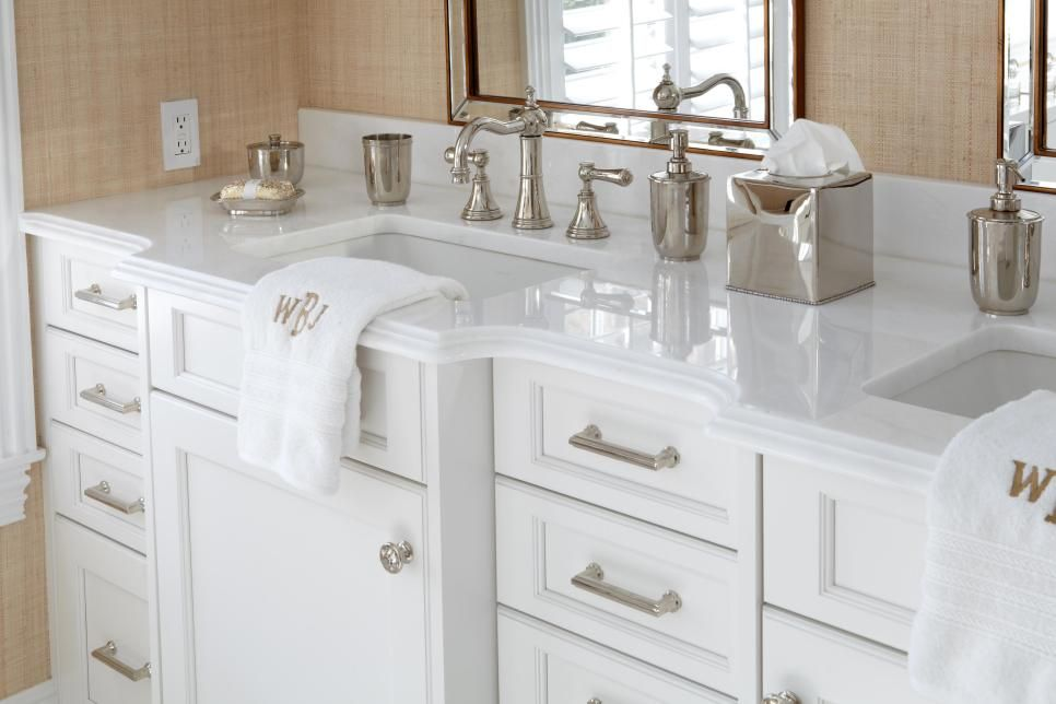 Custom white cabinets, crisp white countertops and textured beige walls create a bright, breezy atmosphere in this beach house bathroom. A traditional faucet with matching countertop accessories adds a classic, elegant touch.