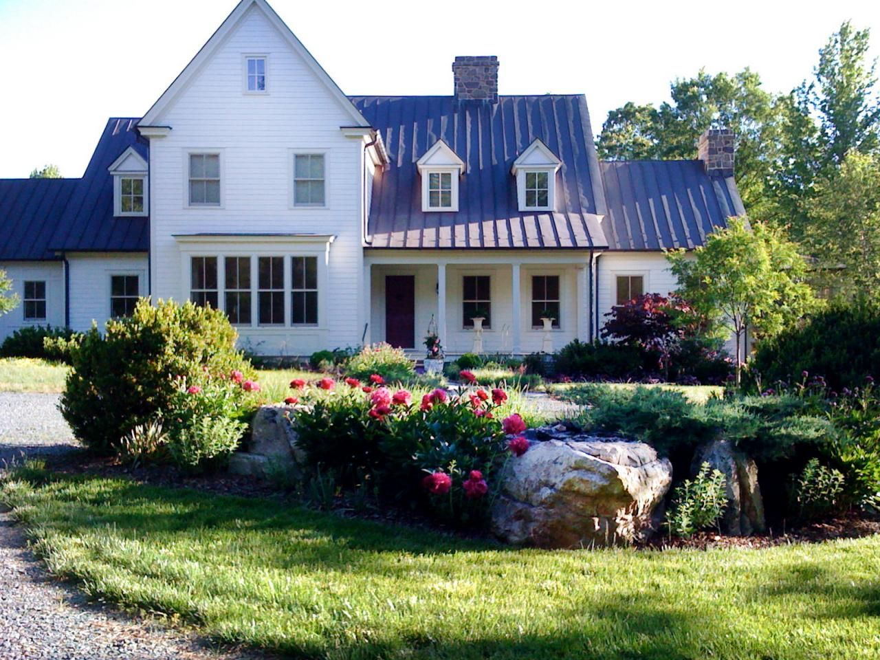 This Front Yard Of Updated Farmhouse Is Landscaped With Lush Grass Large Rocks And
