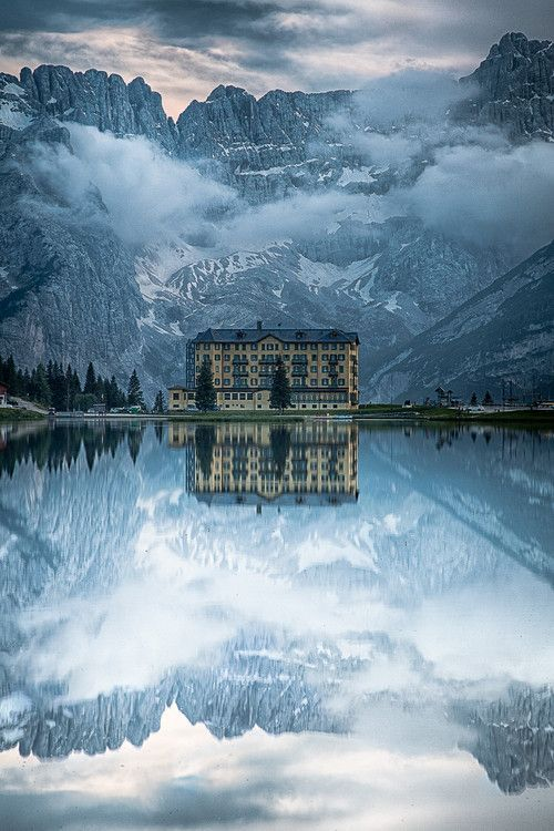 The Grand Hotel reflected in the glassy water of Lake Misurina, Italy