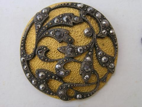 Brass with cut steel button.