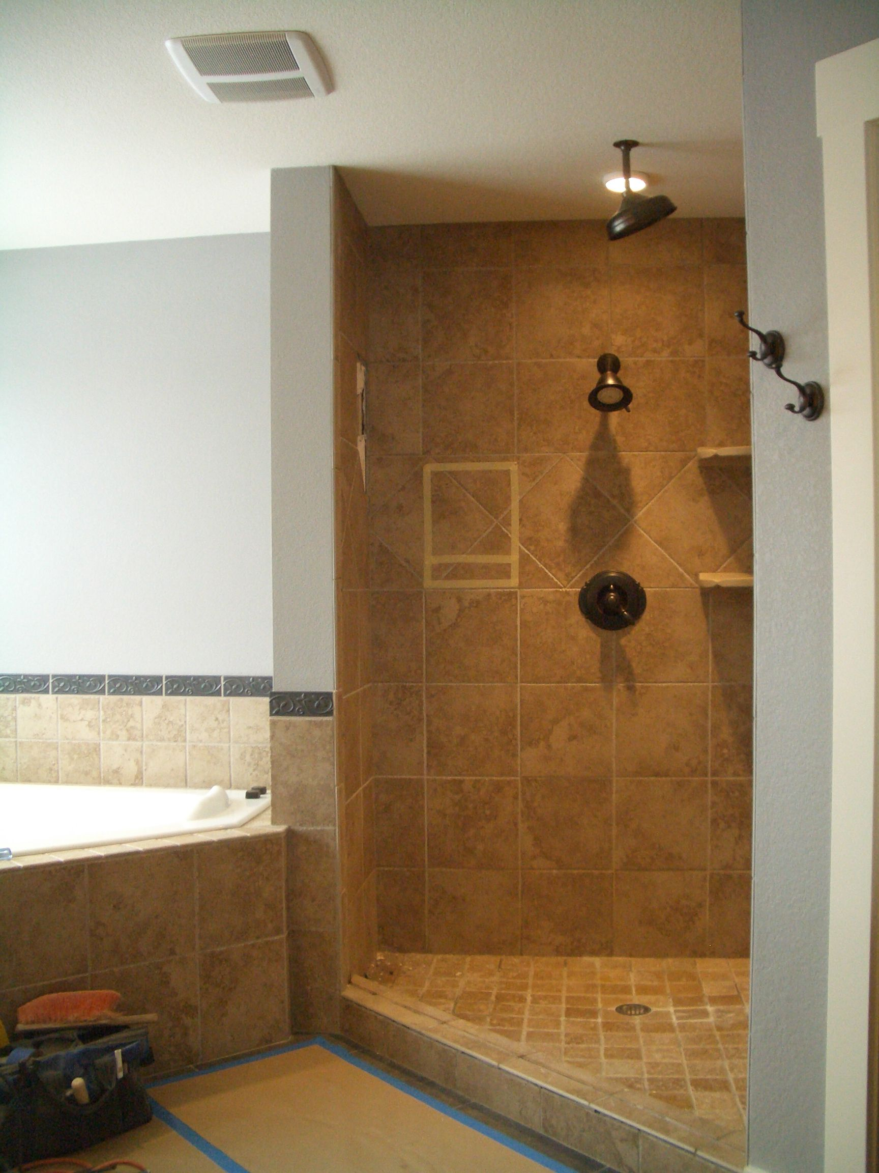 shower bathroom remodel idea with top middle and side shower head with small recessed shelf