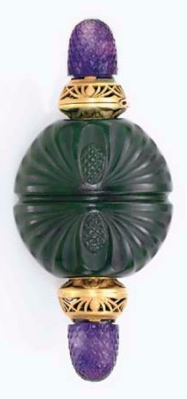 AN ART NOUVEAU NEPHRITE, AMETHYST AND GOLD SCENT BOTTLE, BY BOUCHERON, CIRCA 1900. The circular carved nephrite bottle decorated with pine cone motifs, accented by matte gold chased and openwork terminals, each opening to reveal a nephrite stopper, accented by carved amethyst finials, with French importation marks, signed Boucheron, Paris.