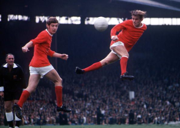 Football 1960's Manchester United's John Fitzpatrick jumps up to head the ball clear with teammate Brian Kidd at Old Trafford