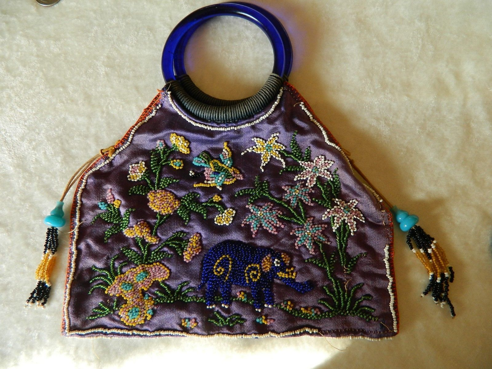 """Antique/Vintage (1901-1919) Asian silk beaded purse w/cobalt blue glass bracelet handles, 2 tassels & a beaded design that includes an elephant, bird & flowers. 10"""" long including the handles x 9"""" wide laying flat. The glass bracelet handles measure 3 1/2"""" diameter & are in good condition; most of the main beaded pattern is good with just a few beads missing. The silk has faded & looks purple to blue, one of the tassel strands is missing & a lot of the white edge beads are missing."""