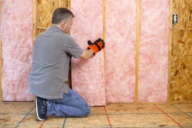 Man Installing Insulation - Don Nichols/E+/Getty Images