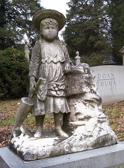 """Referred to by cemetery personal as """"Chunkie"""", this statue appears atop a monument at Spring Grove Cemetery in Cincinnati, Ohio. The cemetery's staff claims that it is the most frequently visited grave in the entire cemetery. Coins, flowers, and small toys are often placed at her feet as an offering."""